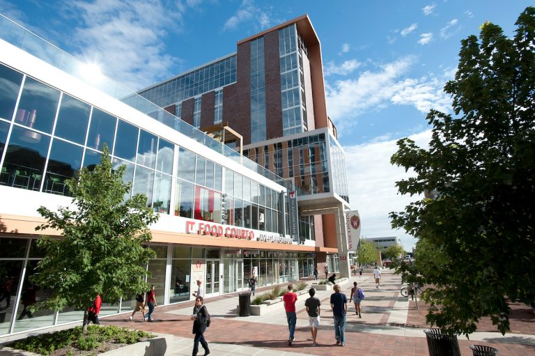 Pedestrians walk past the University Square complex and Student Services Tower at 333 East Campus Mall on a sunny day.