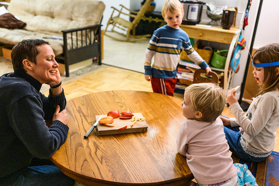 Ash family, mom sits at a table in university housing while her three small children finish eating.