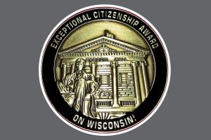 Coin with the Lincoln statue and Bascom Hall and the words Exceptional Citizenship Award On Wisconsin! surrounding it.