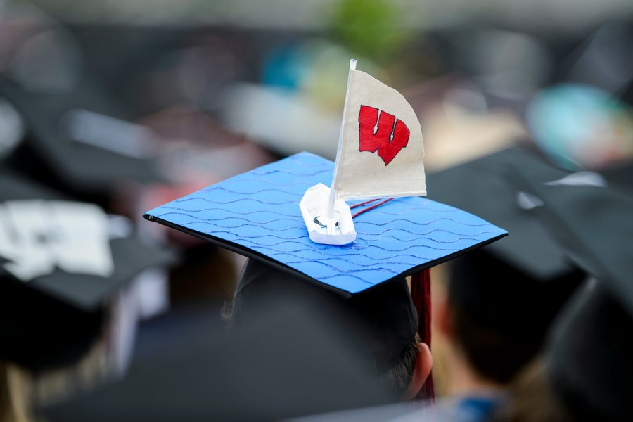 Student at graduation has decorated their hat with a small sailboat that has the University W on the sail.
