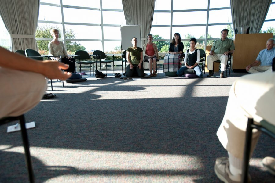 Facilitator seated at center, leads participants during a mindfulness meditation class.