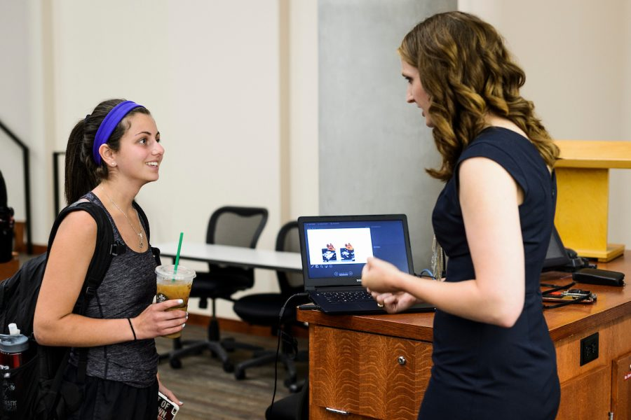 Julie Stamm, associate lecturer of kinesiology in the School of Education, talks with an undergraduate student in front of podium in a classroom.